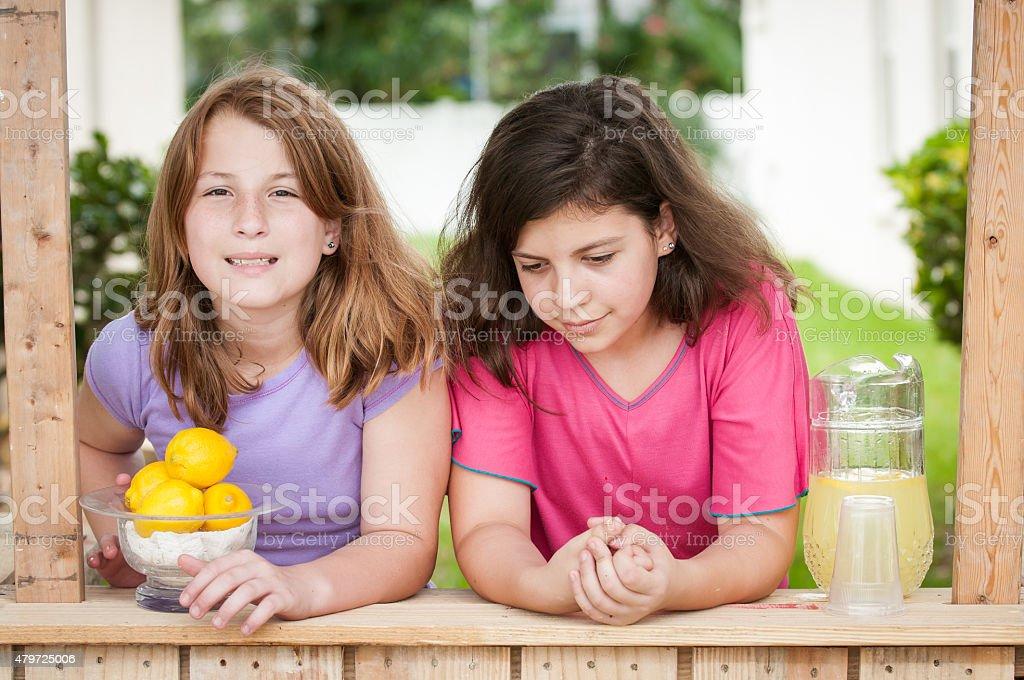 Two young girls selling lemonade stock photo