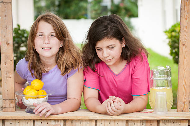 Two young girls selling lemonade stock photo