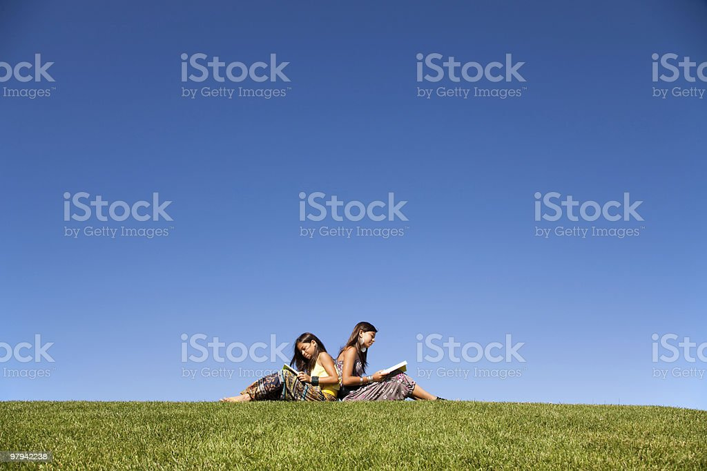 Two young girls sitting back to back in grass and reading royalty-free stock photo