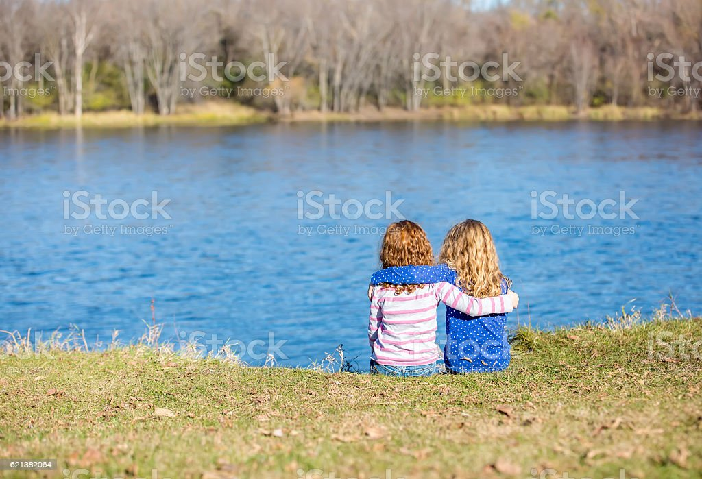Two Young Girls Sitting On Bank of Mississippi River stock photo