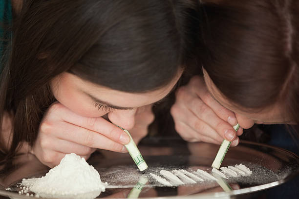 Two young girls snorting an illegal white powder Two young girls snorting an illegal white powder with rolled up dollar bills deathly stock pictures, royalty-free photos & images