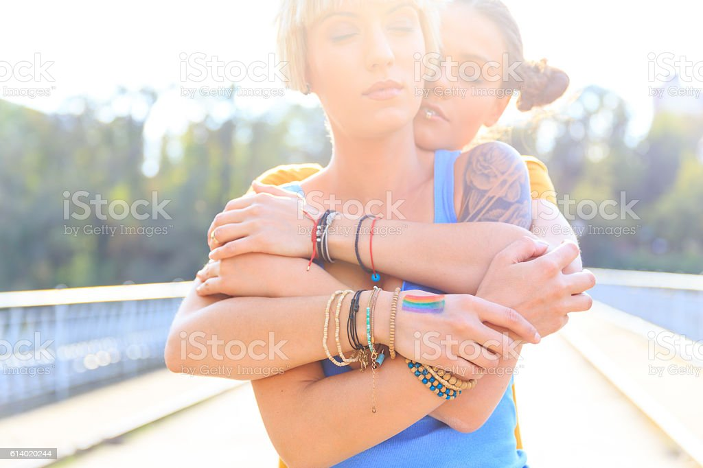 Two young girls standing on bridge and embracing stock photo