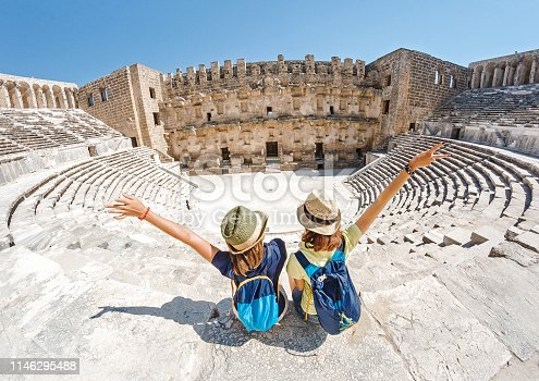 istock Two young girls student traveler enjoy a tour of the ancient Greek amphitheater 1146295488