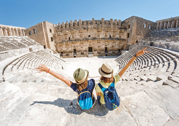 Two young girls student traveler enjoy a tour of the ancient Greek amphitheater stock photo