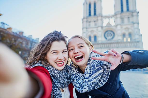 two young girls taking selfie near notre-dame in paris - ikonische frauen stock-fotos und bilder