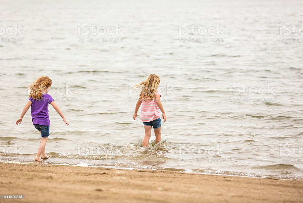 Two Young Girls Wading Into Water at Beach stock photo