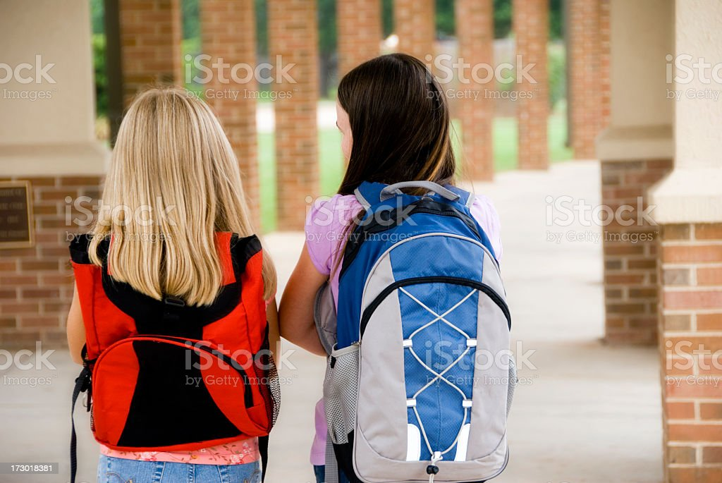 Two young girls walking to school stock photo