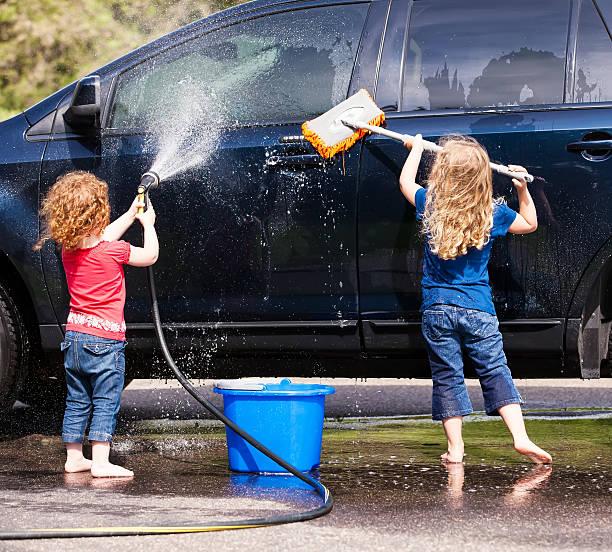 zwei junge mädchen waschen auto - denim caprihosen stock-fotos und bilder