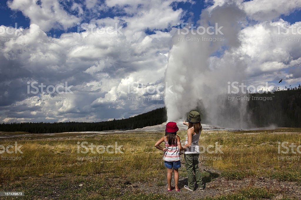 Two young girls watch as Old Faithful is Erupting stock photo