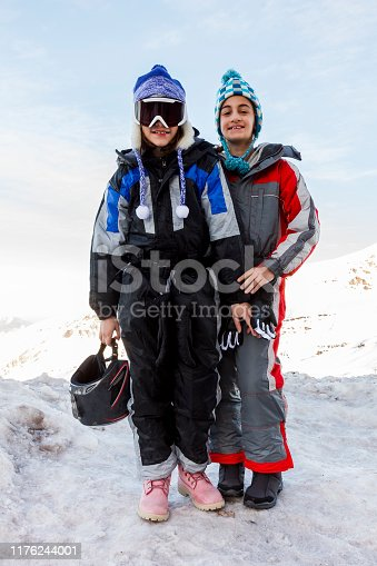 Two young girls wearing ski cloths standing on top of a snow capped mountain in Andes mountain range, Chile
