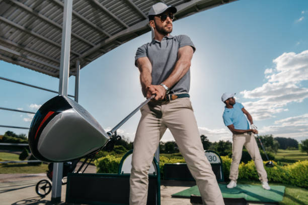 two young golfers with clubs playing golf together - aids healthcare foundation foto e immagini stock