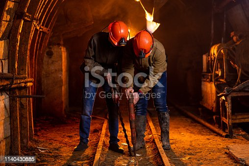 508140747 istock photo Two young guys in a working uniform and protective helmets, carry out work in the mine. Miners 1140430885