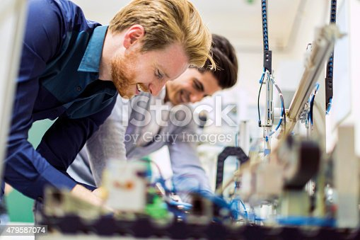 483784268 istock photo Two young handsome engineers working on electronics components 479587074