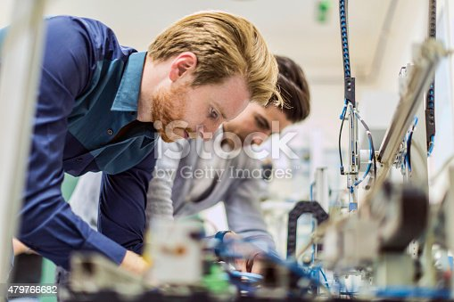 483784268 istock photo Two young handsome engineers working on electronics components 479766682