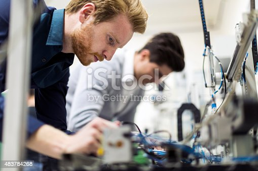 483784268 istock photo Two young handsome engineers working on electronics components 483784268