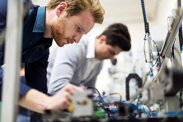 dwa młody przystojny inżynierów pracujących na electronics components - przemysł elektroniczny zdjęcia i obrazy z banku zdjęć