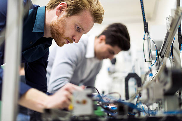 two young handsome engineers working on electronics components - electronics industry stock pictures, royalty-free photos & images