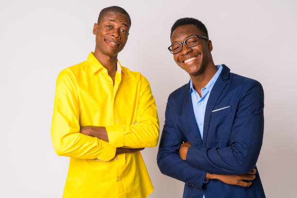 Two young happy African businessmen smiling with arms crossed together stock photo