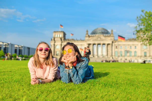 Two Young happy girls wearing sun glasses lying on a grass and have fun in front of the Bundestag building in Berlin. Studying abroad and travel in Germany concept Two Young happy girls wearing sun glasses lying on a grass and have fun in front of the Bundestag building in Berlin. Studying abroad and travel in Germany concept berlin stock pictures, royalty-free photos & images