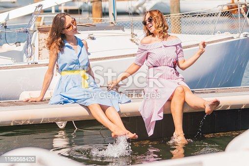 portrait of two girlfriends sitting on jetty