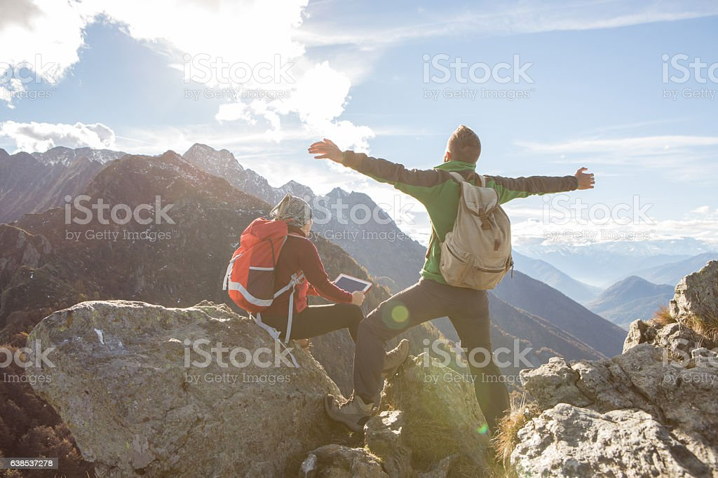 Two young hikers on mountain top looking at digital tablet stock photo