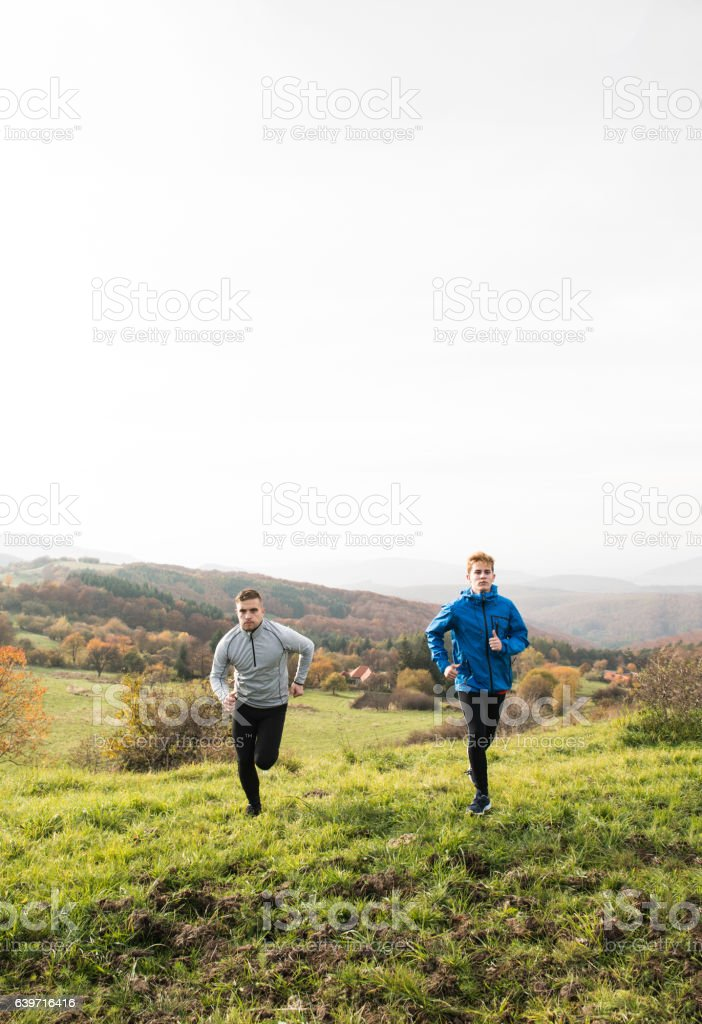 Two young hipster athletes running in sunny autumn nature royalty-free stock photo