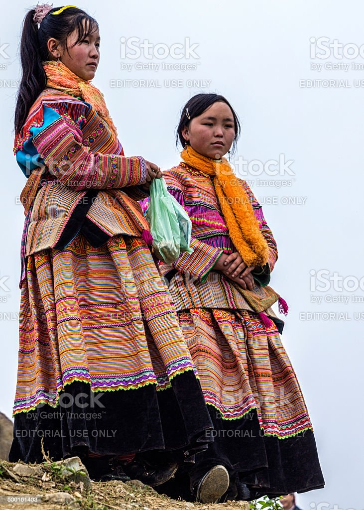 Two young Hmong women show and wait at Sunday market. stock photo