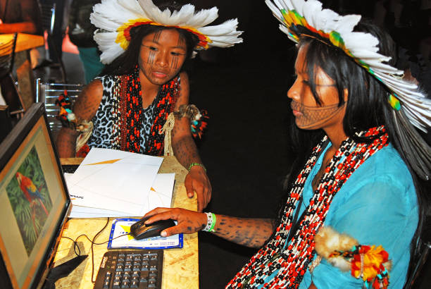 Two young Indigenous Amazonian women working with computers stock photo