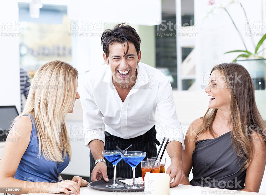 Two young Italian in aperetivo with waiter royalty-free stock photo