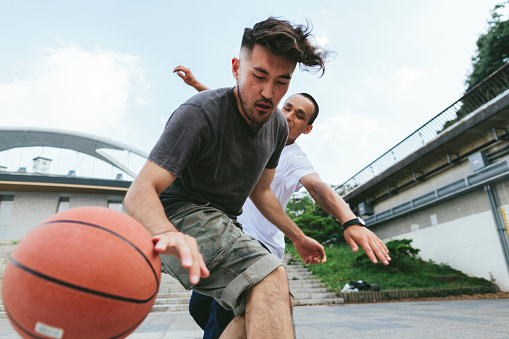 Two young Japanese friends are playing basketball in a public park in Tokyo.