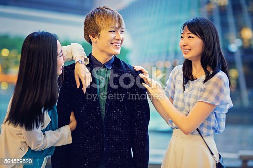 Two young Japanese girls are joking with a guy.