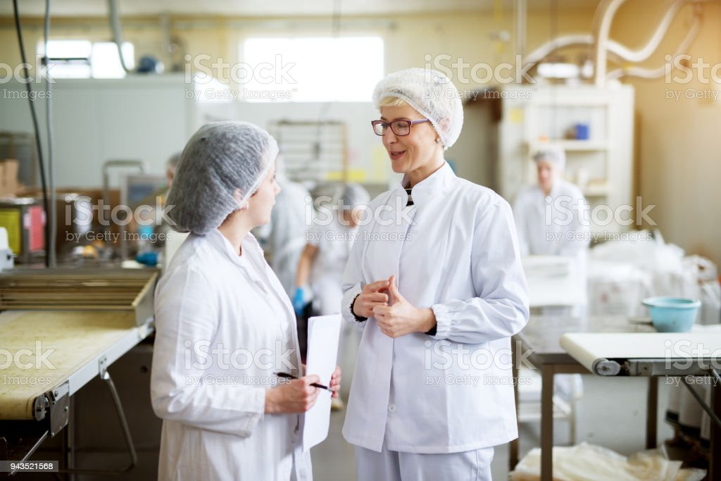 Two young joyful female workers in wearing sterile cloths are discussing statistics of food industry production while one is holding paper sheets. stock photo