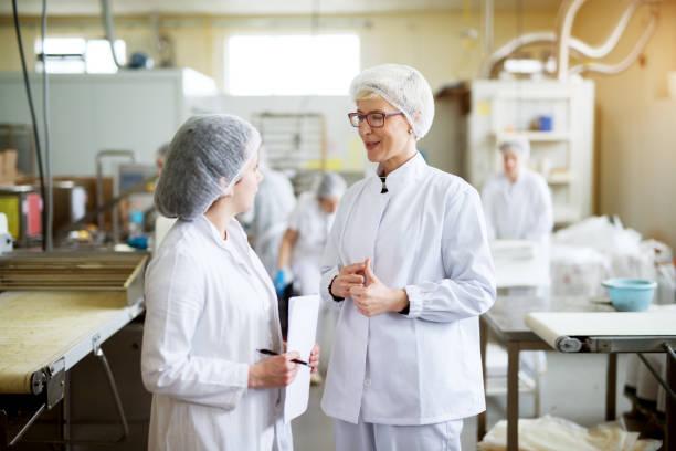 Deux jeunes travailleuses joyeuses vêtu de chiffons stériles discutent des statistiques de la production de l'industrie alimentaire tout en un est maintenant de feuilles de papier. - Photo