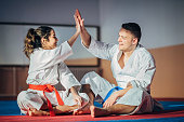 One young woman and one young man, karate students, resting on exercise mat and giving high five after training.