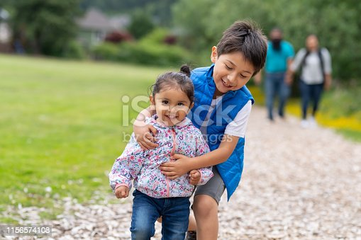 An elementary-age boy and his little sister run along a path out in nature. They're ahead of mom and dad and have big smiles. He's playfully grabbing her as he catches up.