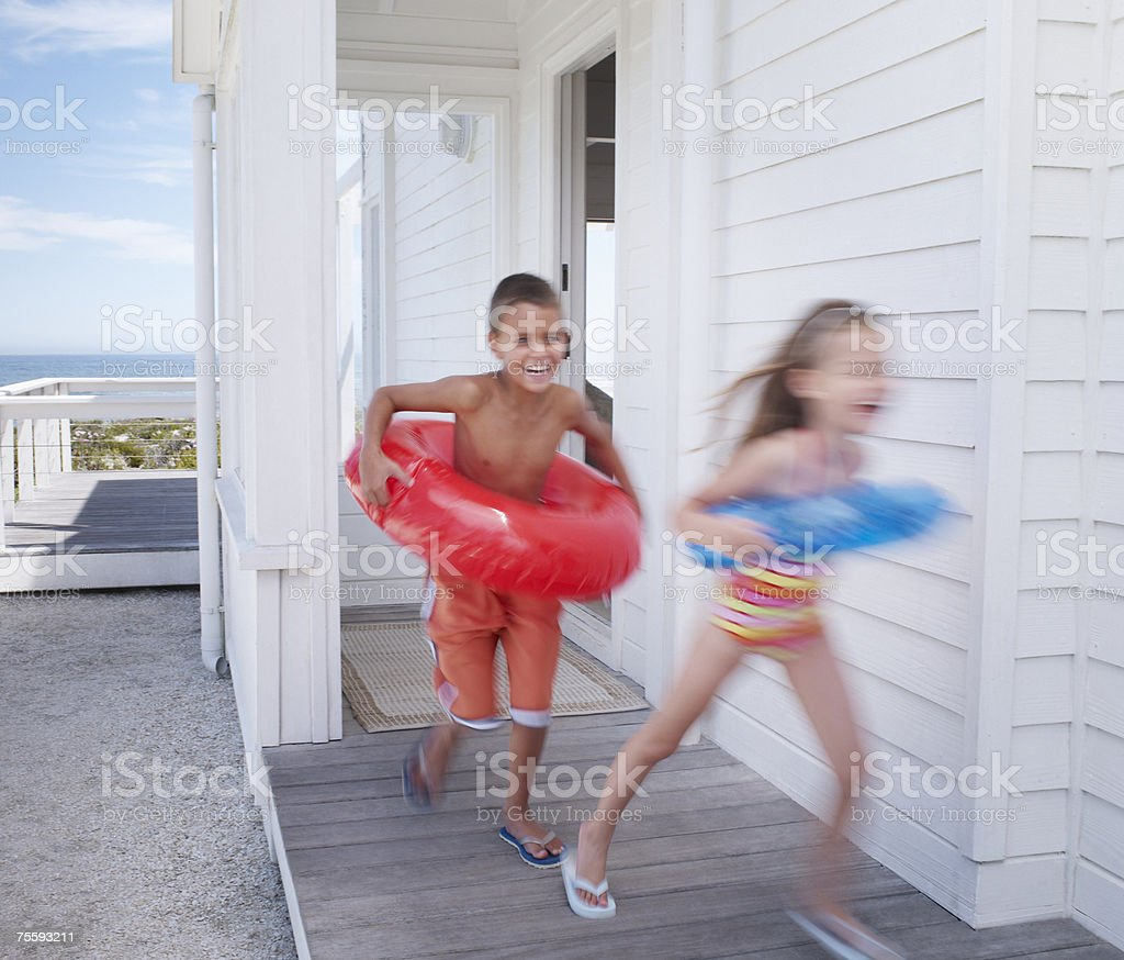 Two young kids leaving a beach house with swimming gear royalty-free stock photo