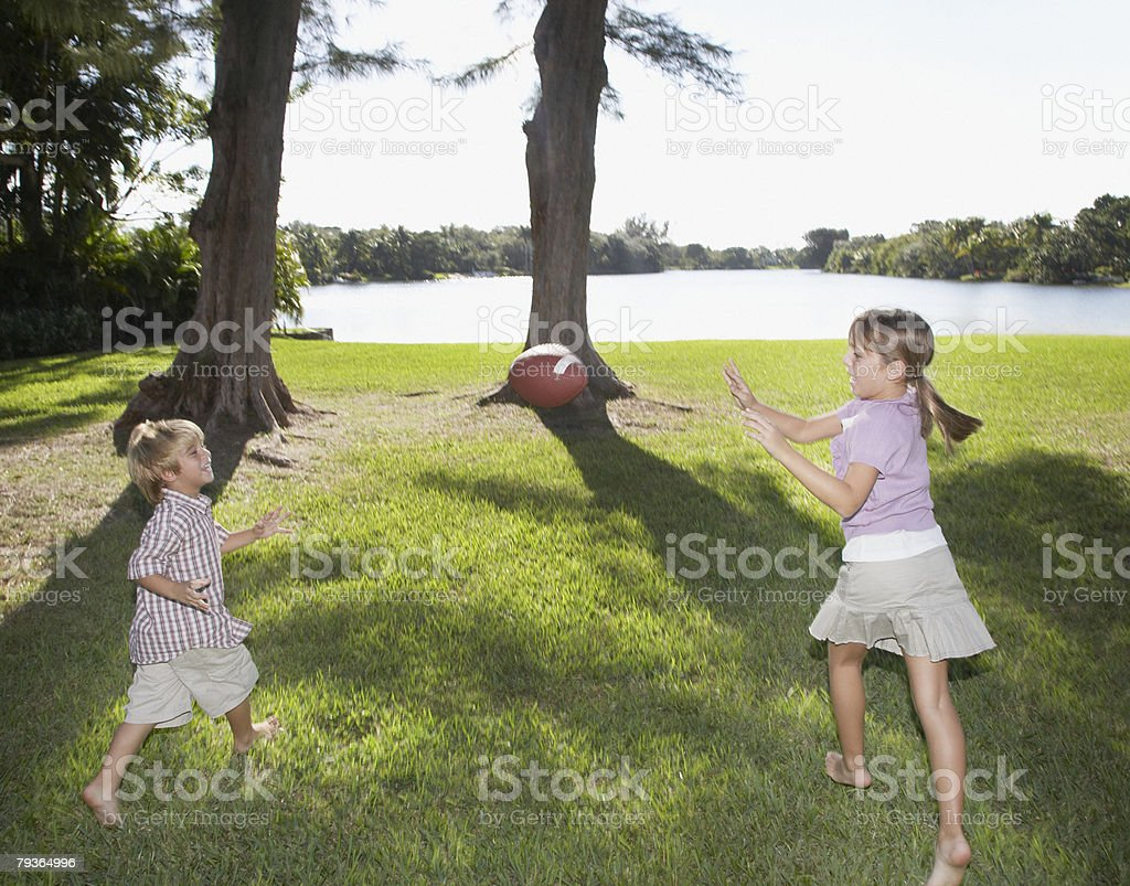 Two young kids playing with a football outdoors at park by a lake 免版稅 stock photo