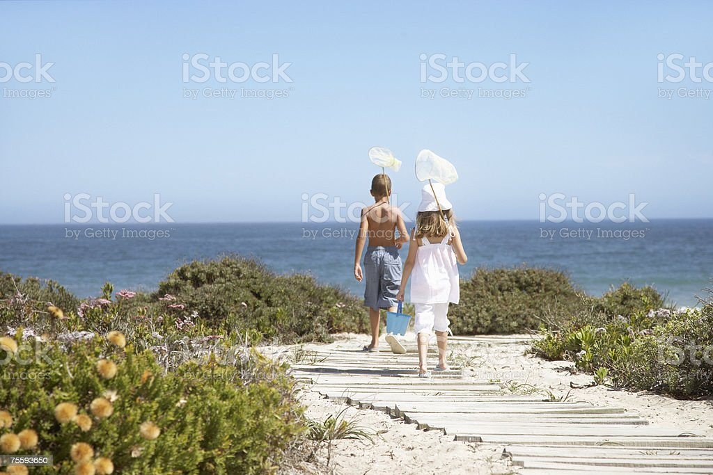 Two young kids with nets walking to the beach royalty-free stock photo