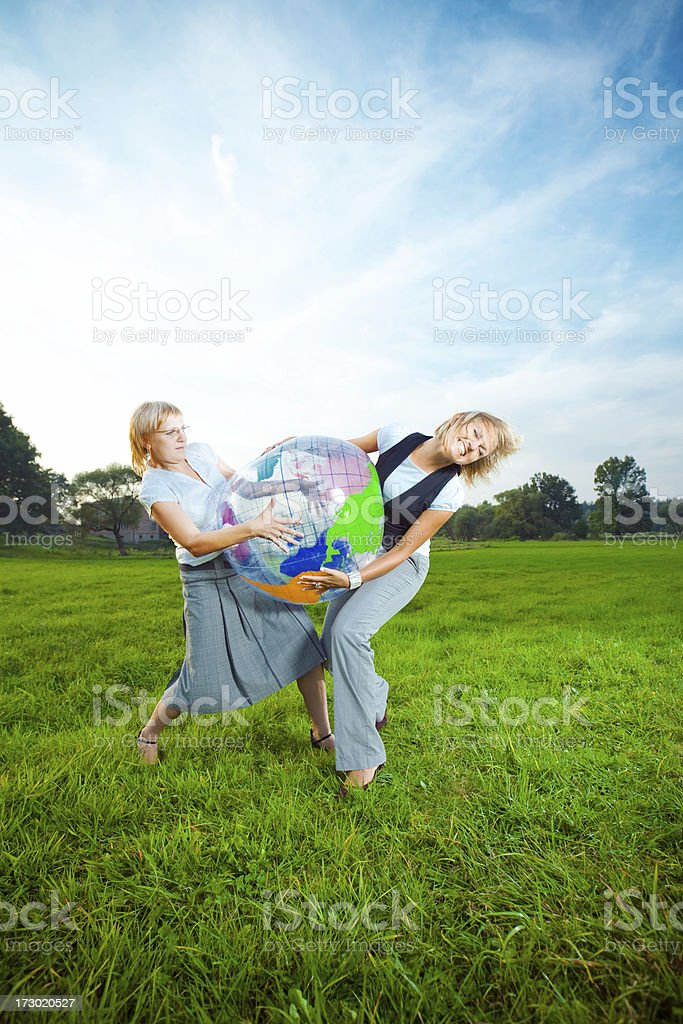 Two young ladies fighting over inflatable globe royalty-free stock photo