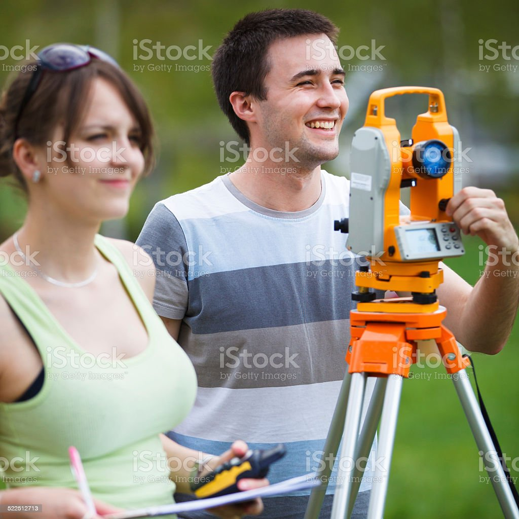 Two young land surveyors at work stock photo