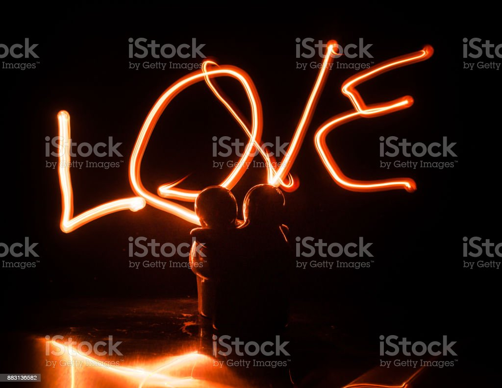 Two young lovers paint a heart on fire. Silhouette of couple and Love words on a dark background stock photo