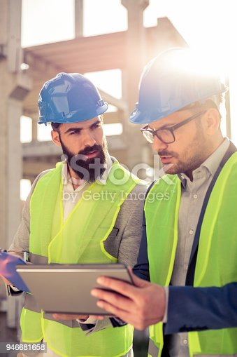1166176793 istock photo Two young male architects or business partners having a meeting and signing documents on a construction site 946681658