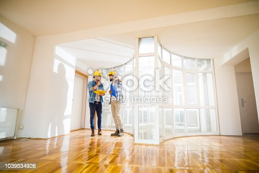 521012560 istock photo Two young male architects walking through an empty apartment a talking about some changes . 1039534926