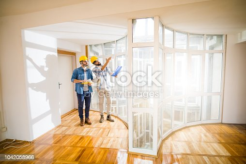 521012560istockphoto Two young male architects walking through an empty apartment a talking about some changes . 1042058966