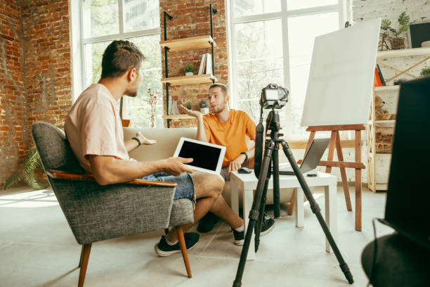 Two young male bloggers with professional camera recording video interview at home stock photo