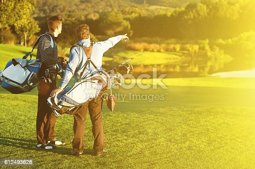Two young men carrying their golf bags on the sunlit course in early morning light stop to point out something distant. Beautiful woods in the background and aple copy space on the fairway..