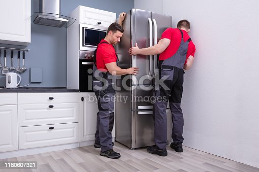 Two Young Male Movers In Uniform Placing Modern Steel Refrigerator In Kitchen