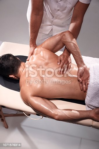 1071579572 istock photo two young man, 20-29 years old, sports chiropractor indoors in studio, photo shoot. Chiropractor pushing muscular mans back with his hands. 1071576314