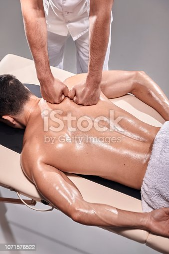 1071579572istockphoto two young man, 20-29 years old, sports physiotherapy indoors in studio, photo shoot. Physiotherapist massaging muscular patient back with his hands, elevated view. 1071576522