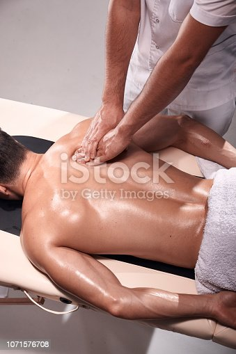 1071579572istockphoto two young man, 20-29 years old, sports physiotherapy indoors in studio, photo shoot. Physiotherapist massaging muscular patient back with his hands, elevated view. 1071576708